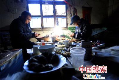 """2016年1月18日,国搜河南报道组一行人前往汝阳刘村探访毛笔的传统制作工艺,在村委会主任刘占河的带领下,首先拜访了村里年龄最大的艺人81岁的刘子敬老先生,老先生13岁就开始学做毛笔,至今已有68年,见到他时,正坐在西厢房小屋里与儿子刘世民在精心制作毛笔,低矮的屋内到处堆满了毛笔材料,几乎无下脚之地,桌子旁一台炉子里生着煤火,暖暖的很温馨。     老先生告诉国搜河南报道组,""""汝阳刘""""毛笔选料考究,仅兔毫的选择标准是秋毫取健,取尖,春夏毫则不要;狼毫的选择就必须要到东北去采集过冬的黄鼠狼尾毛来制作。工艺流程十分独特,主要有:分毛--脱脂--去绒—装毛—齐毛—垫毛—切毛—梳毛—修毛—成头等128道工艺。成品要具备尖、圆、齐、健""""四德"""",软硬适中的标准;其外饰,尤其是笔杆的装饰上更极为讲究,根据笔的形状和高、中、低档的要求配之,既美观又大方。图为河南省项城市孙店镇汝阳刘村81岁的老艺人刘子敬(右)与儿子刘世民在精心制作毛笔。(中国搜索 杨正华摄)"""
