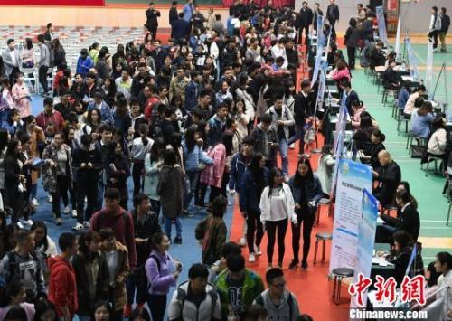 资料图:众多大学生扎堆招聘现场求职。 杨华峰 摄