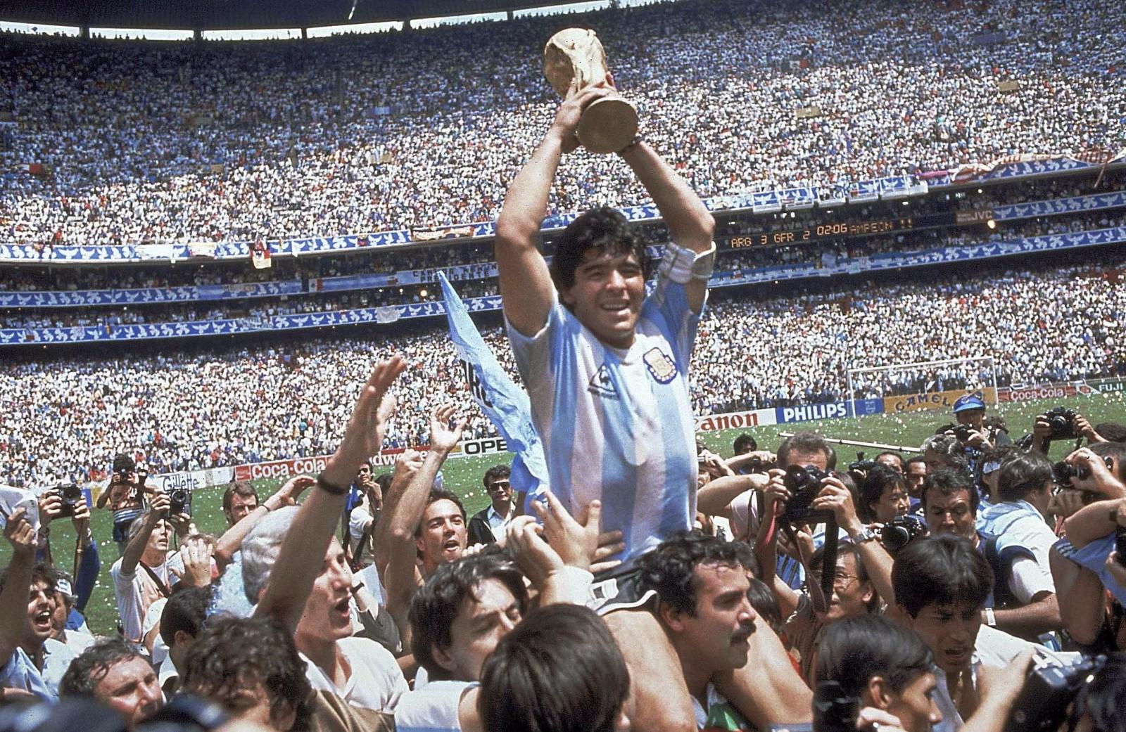 """图为1986年6月29日,阿根廷队在墨西哥世界杯决赛中以3比2战胜西德队,马拉多纳(上)高举大力神杯。马拉多纳在本届比赛四分之一决赛中上演""""上帝之手""""帮助阿根廷队以2比1战胜英格兰队。"""