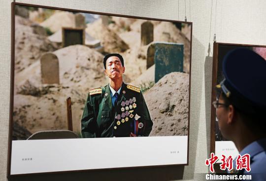 一名部队官兵正在欣赏摄影作品《英雄探妻》。 刘占昆 摄