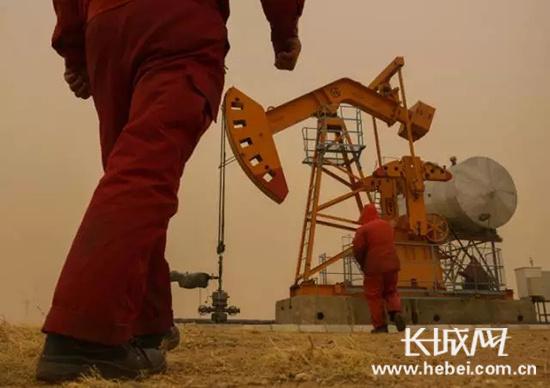 石油员工迎着风沙走向油井.图片