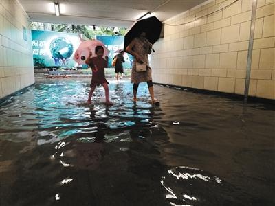 昨日11时许,南三环方庄环岛附近,地下通道里妈妈带着小朋友蹚水前行。新京报实习记者 戴进 摄