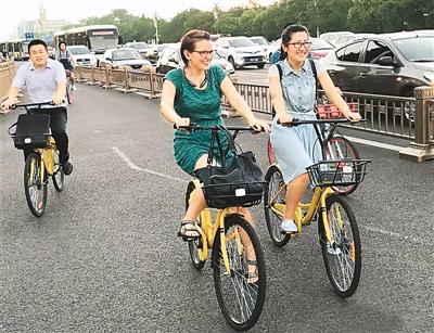 图为几位骑着共享单车的中外人士行进在北京长安街上。   新华社发
